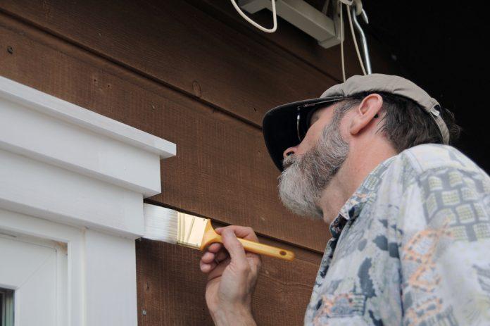 man buiten huis schilderen